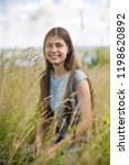 girl in summer in high grass   Shutterstock . vector #1198620892