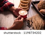 hand is holding a red cup of... | Shutterstock . vector #1198734202