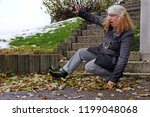 a woman slipped on wet leaves... | Shutterstock . vector #1199048068