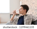young man drinking water at home | Shutterstock . vector #1199461135