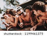 young smiling friends using... | Shutterstock . vector #1199461375
