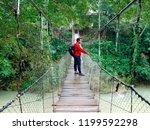 man walking on the suspension... | Shutterstock . vector #1199592298