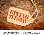 Small photo of Giving Tuesday sign - a paper price tag with a twine on a rustic wood