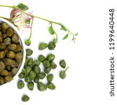 Small photo of Capers. Pickled capers, raw bud and caper plant on white background, top view
