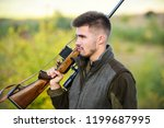 man bearded hunter with rifle... | Shutterstock . vector #1199687995