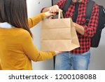 Small photo of Anonimous delivery food service at home - you can eat the restaurant food where you prefer at home or at the office - anonimous bag with food order from the people - shopping bag - n-cov19 Coronavirus