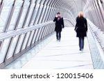 silhouette of business people walking over a pedestrian bridge in Paris, La Defense - stock photo