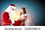 Portrait of Santa Claus with a little girl looking at a gift - stock photo
