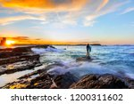 surfer standing on the end of a ... | Shutterstock . vector #1200311602