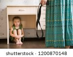 Small photo of Domestic violence. Mother holding the belt in her hand to punish her small daughter. Scared child hiding under a table and sitting there terrified by physical punishment. Shallow depth of field