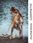 Small photo of Angry caveman, manly boy with stone axe and bow hunting near river. Prehistoric tribal boy outdoors on nature. Young shaggy and dirty savage, warrior and hunter with weapon. Primitive ice age man in