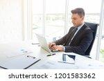 handsome businessman working at ... | Shutterstock . vector #1201583362