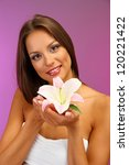 beautiful young woman with lily, on purple background - stock photo
