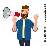man holding a megaphone... | Shutterstock .eps vector #1202222155