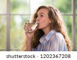 healthy young woman drinking... | Shutterstock . vector #1202367208