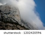 Clouds form on the East side of the Rock of Gibraltar. Gibraltar is a British Overseas Territory located on the southern tip of Spain. - stock photo