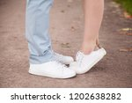 Loving woman standing tiptoe, trying kiss boyfriend outdoors in park, couple in love in jeans and white sneakers embracing, hugging on street, small girlfriend and tall man, romance moment close up
