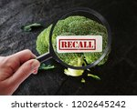 Small photo of Hand with magnifying glass looking at broccoli Recall label