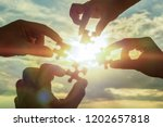 collaborate four hands trying... | Shutterstock . vector #1202657818