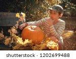 young european boy in stripy... | Shutterstock . vector #1202699488