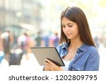 serious teen is using a tablet... | Shutterstock . vector #1202809795