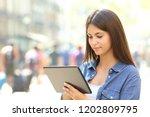 serious teen is using a tablet... | Shutterstock . vector #1202809795