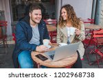 couple sitting in cafe with... | Shutterstock . vector #1202968738