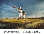 American football player receiving a pass during a team practice on a football field against a moody afternoon sky