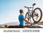 man take his bicycle from car... | Shutterstock . vector #1203313408