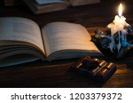Stock photo romance book of poems black porous chocolate and a candle on a brown wooden background 1203379372
