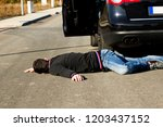 the man lies on the road behind ...   Shutterstock . vector #1203437152