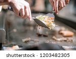 hand of man take cooking of... | Shutterstock . vector #1203482305