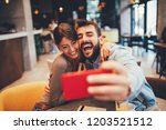 young happy couple at a date... | Shutterstock . vector #1203521512