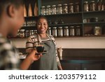 smiling young african barista... | Shutterstock . vector #1203579112