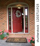 Small photo of A brick residence with an open front door and a large welcome mat. Flowers in pots stand on either side of the entrance and a white flower wreath hangs on the red door.