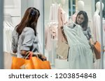 happy asian woman choosing... | Shutterstock . vector #1203854848
