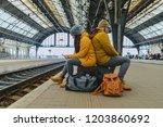 bored couple sit on their bags... | Shutterstock . vector #1203860692
