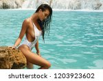 sexy woman in white swimsuit is ...   Shutterstock . vector #1203923602