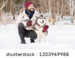 Stock photo full length portrait of modern asian man posing with gorgeous husky dog sitting down outdoors in 1203969988