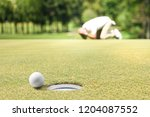 Small photo of Man golfer feeling disappointed after a putted golf ball missed the hole