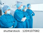 side view of surgical team in... | Shutterstock . vector #1204107082