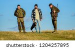 men carry hunting rifles.... | Shutterstock . vector #1204257895