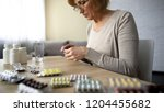 senior lady opening pills... | Shutterstock . vector #1204455682