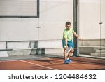 man playing padel in a orange... | Shutterstock . vector #1204484632