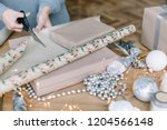 woman in cozy sweater wrapping... | Shutterstock . vector #1204566148