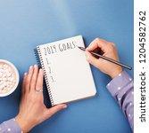 woman's hand writing 2019 goals ... | Shutterstock . vector #1204582762
