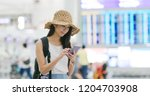 woman checking flight number on ...   Shutterstock . vector #1204703908