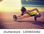 sportswoman stretching before... | Shutterstock . vector #1204833382