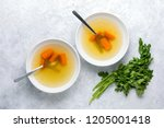 Bouillon or broth served in two white bowls, view from above