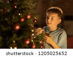 cheerful boy decorating his... | Shutterstock . vector #1205025652